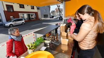 Zwei Lernende bereiten das Essen im Food-Truck zu.