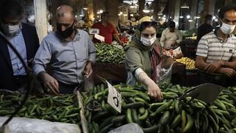 Kunden mit Schutzmasken kaufen Gemüse auf dem Basar von Zandschan ein. Wegen des dramatischen Anstiegs der Anzahl der täglichen Corona-Toten und Neuinfektionen hat Präsident Ruhani eine Maskenpflicht in Behörden, im öffentlichen Nahverkehr sowie aufn überdachte Flächen von Einkaufszentren angeordnet. Foto: Vahid Salemi/AP/dpa