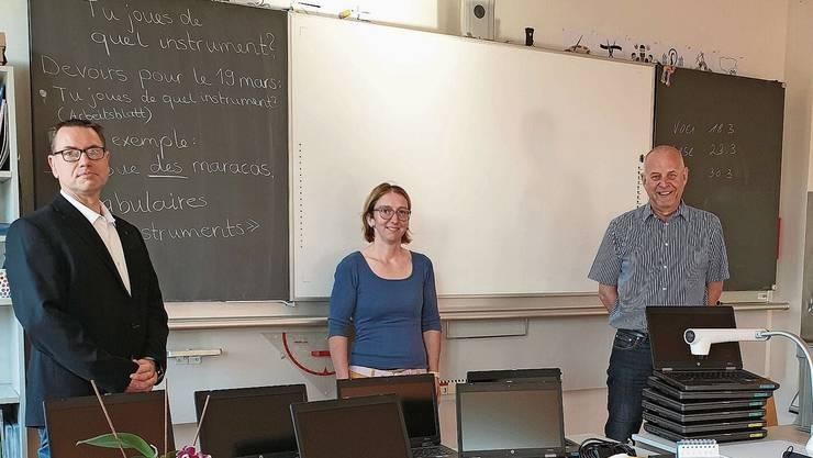 Thorsten Ebbinghaus (v.l.), Sandra Hauri, Präsidentin der Schulpflege, und Schulleiter Martin Steinacher bei der Geräteübergabe.