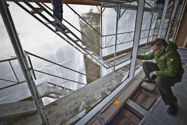 Architekt Tim Wieland kontrolliert den im Erker montierten Fensterrahmen