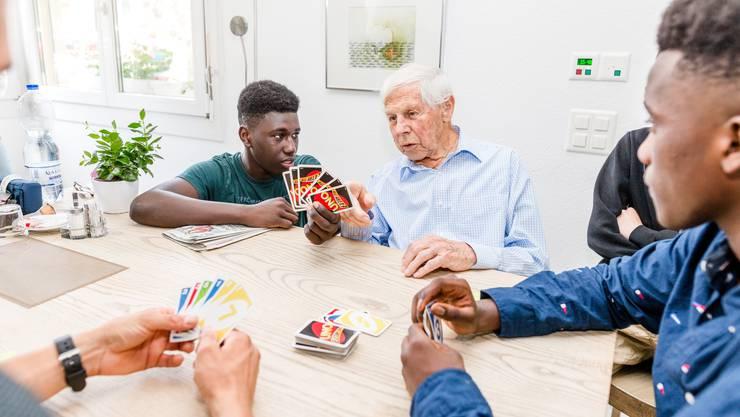 Der 17-jährige Gambier, Assan Sowe, hilft dem 91-jährigen Ernst Frischknecht beim UNO spielen.