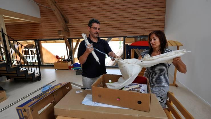 Thomas Steiner, Präsident der Kindertagesstätte und deren Leiterin Monika Crausaz packen eine Baby-Schaukel aus.