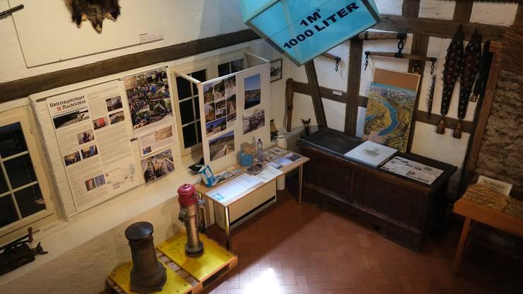 Nur wenige Tage nach dem Spatenstich des Reservoirs «Holebeeren» im Gubrist ist das Ereignis schon im Museum verewigt (links an der Wand).