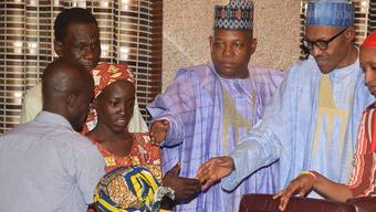 Das erste von Boko Haram entführte Mädchen (links), das freigekommen ist, wird vom nigerianischen Präsidenten Buhari (rechts) empfangen. Ein zweites Mädchen soll mittlerweile gefunden worden sein.