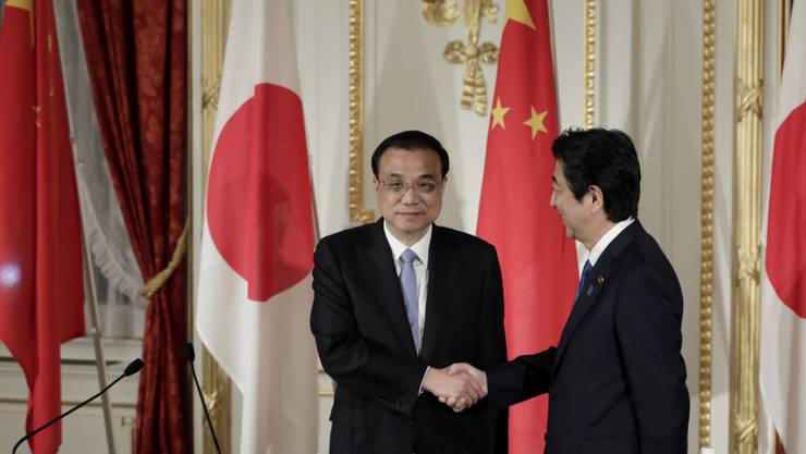 Handschlag als Symbol für das Tauwetter zwischen Peking und Tokio: Der japanische Premierminister Shinzo Abe (r) und sein chinesischer Amtskollege Li Keqiang (l) an einer gemeinsamen Medienkonferenz in Tokio.