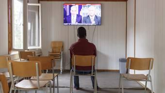Ein Asylbewerber verfolgt in seiner Unterkunft die Nachrichtensendung.