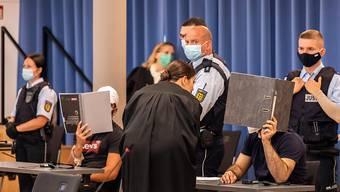 dpatopbilder - Zwei Angeklagte halten während des Prozesses in Freiburg Mappen als Sichtschutz vor ihre Gesichter. Foto: Philipp von Ditfurth/dpa - ACHTUNG: Person(en) wurde(n) aus rechtlichen Gründen gepixelt