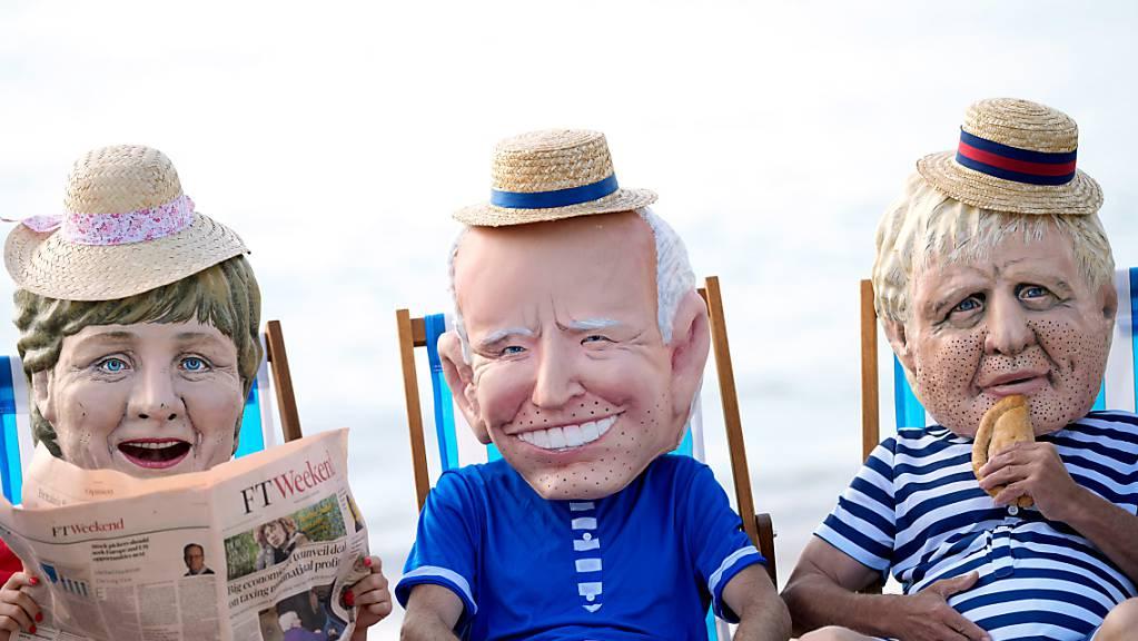 Klimaaktivisten von Oxfam, die riesige Köpfe tragen, die die Staats- und Regierungschefs der G7 (l-r) Bundeskanzlerin Angela Merkel, US-Präsident Joe Biden, der britische Premierminister Boris Johnson darstellen sollen, sitzen auf Strandliegen, während sie an einer Aktion am Swanpool Beach teilnehmen. Foto: Alastair Grant/AP/dpa