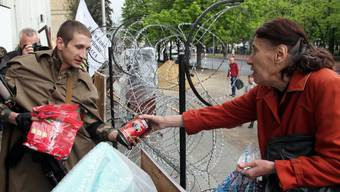 Eine ältere Frau verteilt in Lugansk Essen an die pro-russischen Aktivisten.