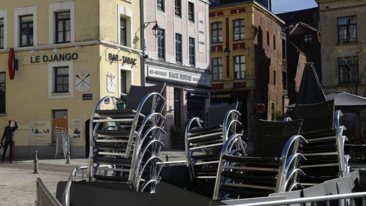 Gestapelte Stühle vor einem Café in Lille. Foto: Michel Spingler/AP/dpa