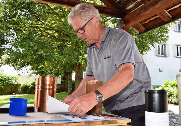Kirchenpflegemitglied Ernst Rauber legt die Dokumente in die Dosen
