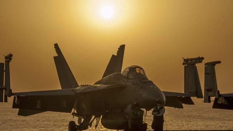 Kampfjet auf dem Deck eines US-Flugzeugträges: Die US-geführte Koalition hat am Samstag im Kampf gegen Dschihadisten Ziele in der syrischen Stadt angegriffen (Archivbild).