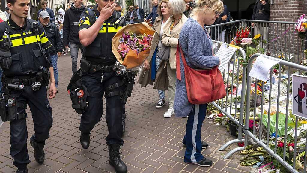 dpatopbilder - Polizisten bringen einen Blumenstrauß zu dem Blumenmeer für den Reporter Peter R. de Vries. Foto: Evert Elzinga/ANP/dpa
