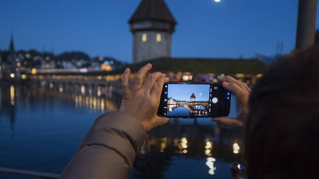 Eine asiatische Touristin macht ein Foto der Kapellbruecke mit dem Smartphone in der Altstadt von Luzern. (Archivbild)