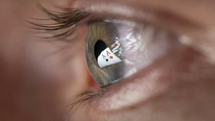 Zwei Ass-Spielkarten spiegeln sich in der Pupille eines Mannes, der Online-Poker spielt. Künftig dürfen auch Schweizer Casinos Online-Spiele anbieten.