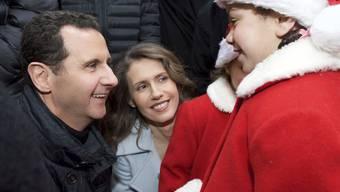 Der syrische Präsident Baschar al-Assad (links) und seine Ehefrau Asma (Mitte) begrüssen als Weihnachtsmänner verkleidete christliche Waisen in Sednaja nördlich von Damaskus (in einer Aufnahme vom Sonntag, wie sie auf der Facebook-Seite des syrischen Präsidialamtes erschien).