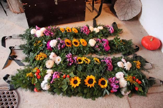 Überall liegen die von Christine Lisser und ihrer Schwägerin Conny Lisser kreierten Bauchkränze bereit. Blumen wurden kunstvoll auf alte Feuerwehrschläuche drapiert, die mit alten Sicherheitsgurten umgebunden werden