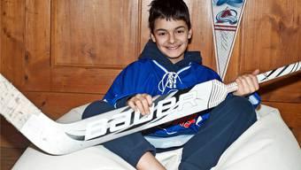 Nils Perrig zeigt in seinem Zimmer seinen Eishockeystock und das Trikot, das er in Kanada tragen wird. Patricia Schoch