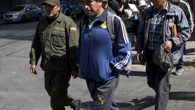 Bergarbeiter werden in La Paz zur Befragung abgeführt. Die in Genossenschaften zusammengeschlossenen Arbeiter protestieren seit Anfang August gegen ein neues Gesetz, nach dem sich ihre Mitglieder Gewerkschaften anschliessen dürfen.