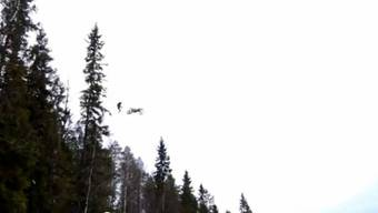 Der Mottorradfahrer springt über einen Wald in einen Fluss.