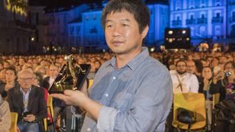 Der chinesische Regisseur Wang Bing mit seinem Goldenen Leoparden. Er war darüber genauso überrascht wie Kritiker und Publikum und hatte deshalb keine Dankesrede vorbereitet.