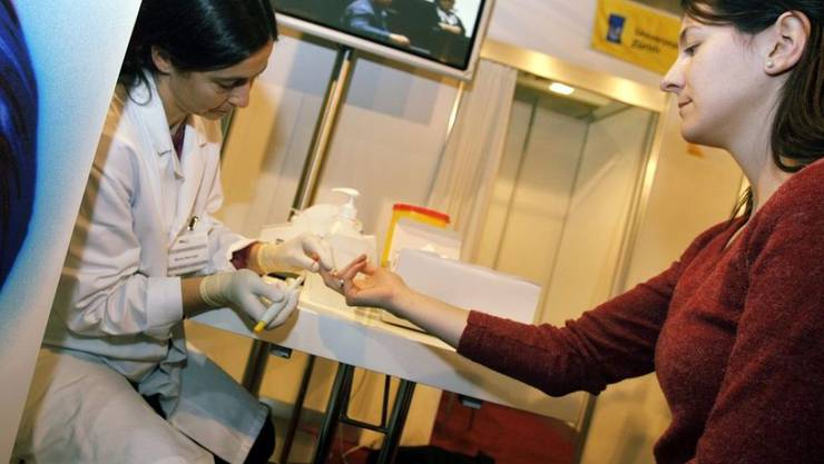 Eine Probandin lässt den Cholesterin-Spiegel untersuchen. Gemäss einer Studie des Swiss Medical Board liesse sich die Zahl der Herzinfarkte senken, wenn das Blutfett senkende Mittel Statin so angewendet würde, wie Fachgesellschaften es empfehlen. (Archivbild)