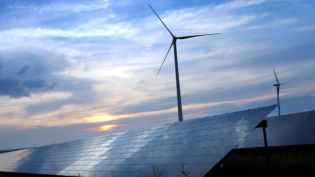 Der mit Wolken überzogene Abendhimmel spiegelt sich auf den Solarzellen einer vor Windrädern stehenden Solarkraftanlage.