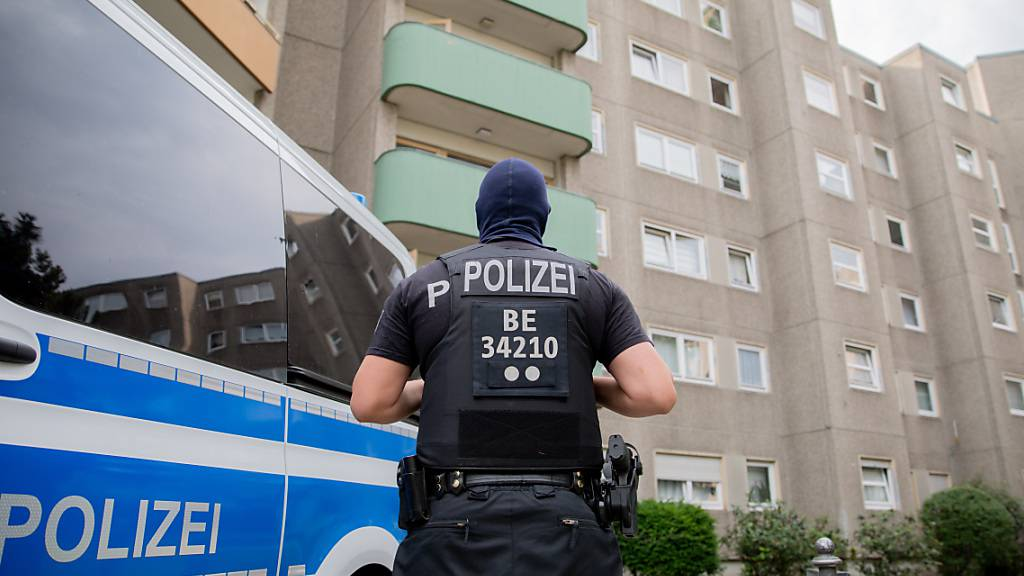 Ein Polizist steht bei einem Polizeieinsatz im Rahmen einer groß angelegten Razzia gegen Tatverdächtige aus der islamistischen Szene in Berlin-Gesundbrunnen vor einem Gebäude. Foto: Christoph Soeder/dpa