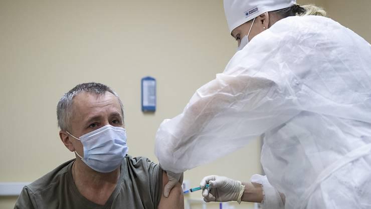 Eine medizinische Mitarbeiterin verabreicht einem Mann den Corona-Impfstoff Sputnik V. Foto: Pavel Golovkin/AP/dpa