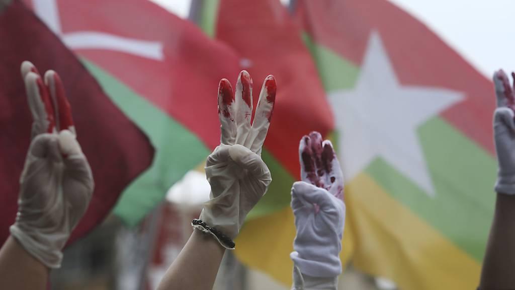 Myanmarische Demonstranten die in Taiwan leben, tragen rot bemalte Handschuhe und zeigen den symbolischen Drei-Finger-Gruß bei einem Protest gegen das Militärregime in Myanmar.(Symbolbild) Foto: Chiang Ying-Ying/AP/dpa