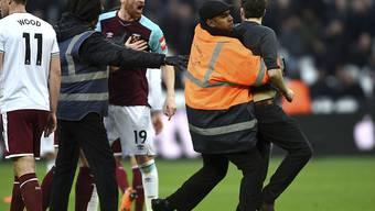 Ein auf den Platz gestürmter Fan legt sich mit West Hams Innenverteidiger James Collins an, ehe er abgeführt wird