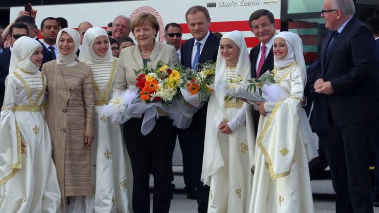 Angela Merkel, Donald Tusk, Ahmet Davutoglu und Frans Timmermans wurden von Flüchtlingen in traditioneller Tracht mit Blumen in Empfang genommen.