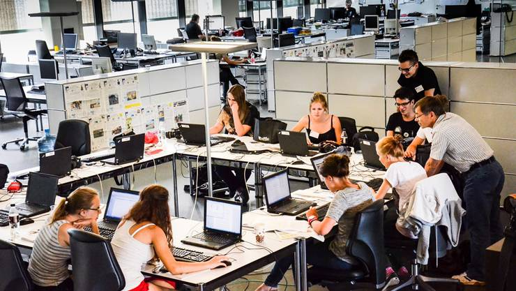 Die Arbeitsplätze der jungen Leute stehen mitten im Newsroom.