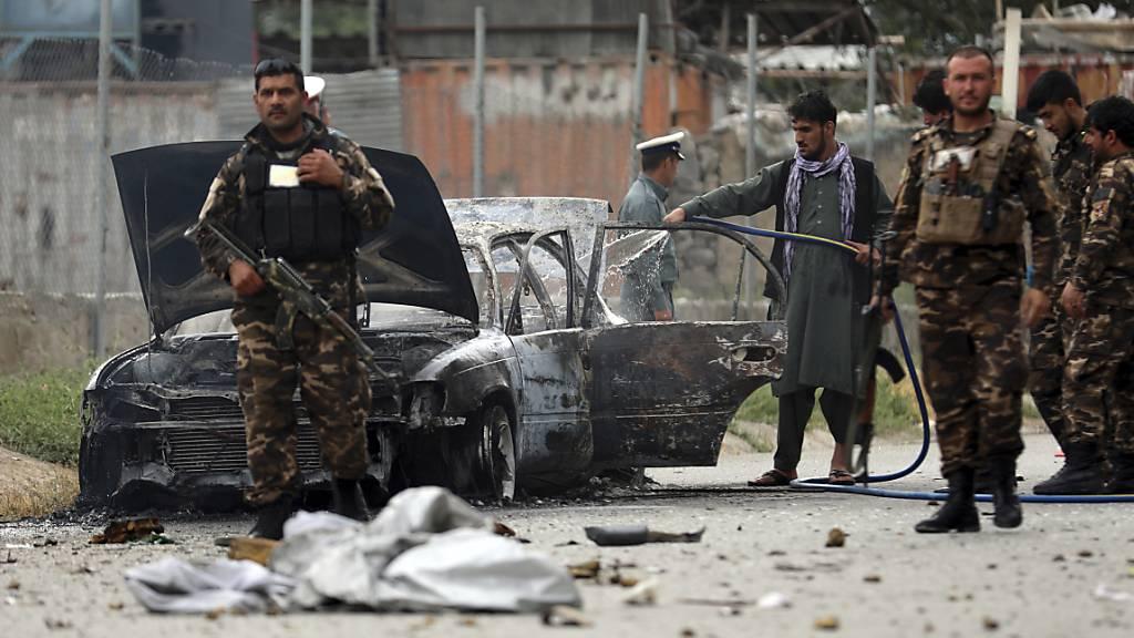 Sicherheitskräfte inspizieren das Wrack eines Fahrzeugs, das Raketen abgefeuert hat. Foto: Rahmat Gul/AP/dpa