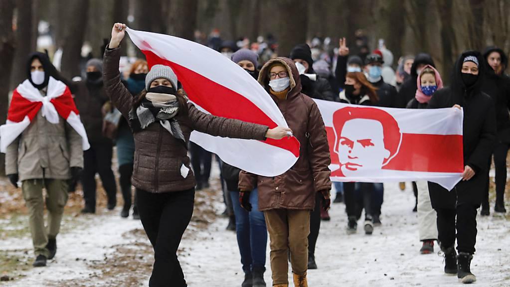 Demonstranten mit Mund-Nasen-Schutz tragen bei einer Kundgebung, auf der sie den Rücktritt von Machthaber Lukaschenko fordern, Fahnen in den Farben der früheren belarussischen Nationalflagge.