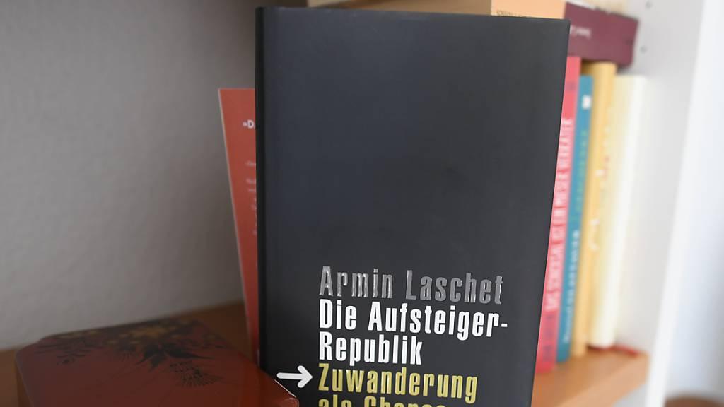 Das Buch von Armin Laschet «Die Aufsteiger Republik-Zuwanderung eine Chance» steht in einem Regal. Foto: Roberto Pfeil/dpa