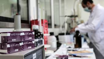 ARCHIV - Ein Mitarbeiter des ägyptischen Pharmaunternehmens «Eva Pharma» arbeitet an der Produktion des Wirkstoffs Remdesivir, einem antiviralen Breitspektrum-Medikament, während Packungen des Medikaments neben ihm liegen. Foto: Fadel Dawood/dpa