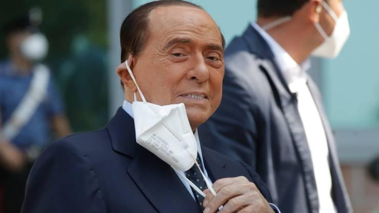 ARCHIV - Silvio Berlusconi, ehemaliger Ministerpräsident von Italien, nimmt seinen Mund-Nasen-Schutz ab, nachdem er das Krankenhaus San Raffaele verlassen hat. Berlusconi war ins Krankenhaus eingeliefert worden, um seine Corona-Infektion zu überwachen, nachdem er positiv auf Covid-19 getestet worden war. Foto: Luca Bruno/AP/dpa