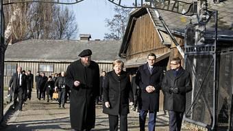 """Die deutsche Kanzlerin Angela Merkel am Freitag im ehemaligen deutschen Konzentrationslager Auschwitz beim berüchtigten Tor mit dem zynischen Schriftzug """"Arbeit macht frei""""."""