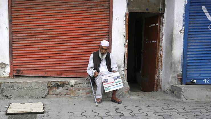 Ausgangssperre in Srinagar: Ein Mann liest vor einem geschlossenen Geschäft in der Sommerhauptstadt von Jammu und Kashmir eine Zeitung.