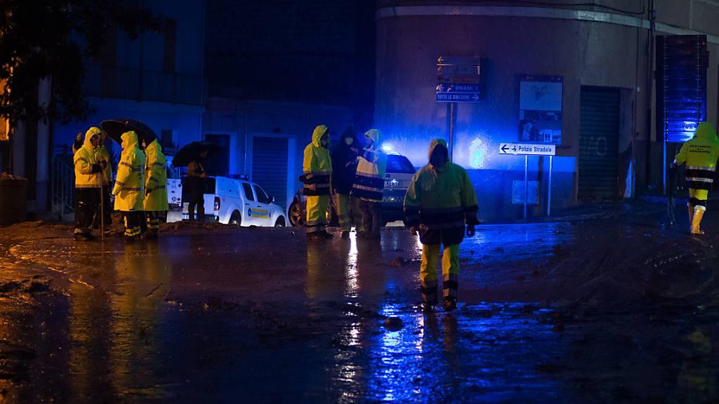 Rettungskräfte stehen an einer mit Schlamm überzogenen Straße. Foto: Alessandro Tocco/LaPresse via ZUMA Press/dpa
