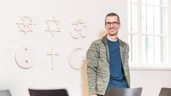 Gefängnispfarrer Mark Schwyter im Mehrzweckraum in der Justizvollzugsanstalt Lenzburg, vor der Wand mit den Symbolen der grossen Weltreligionen.
