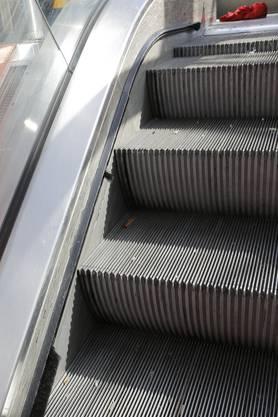 Die Sockelbürsten, ein Einklemmschutz, sind die Bürsten links neben den Tritten. Im oberen Bereich der Treppe sind die abgerissen. Daher entschieden die SBB, die Rolltreppe aus Sicherheitsgründen abzuschalten.