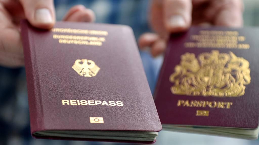ARCHIV - Ein britischer und ein deutscher Reisepass werden in die Kamera gehalten. Foto: Britta Pedersen/zb/dpa