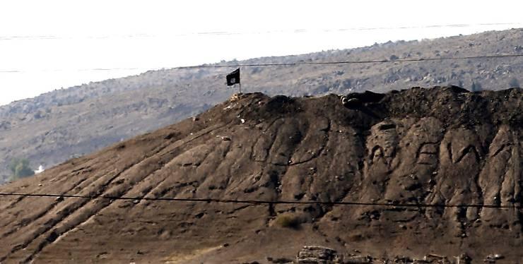 Eine Flagge der Terrorgruppe Islamischer Staat weht auf einem Hügel in der Nähe der Stadt Kobane.