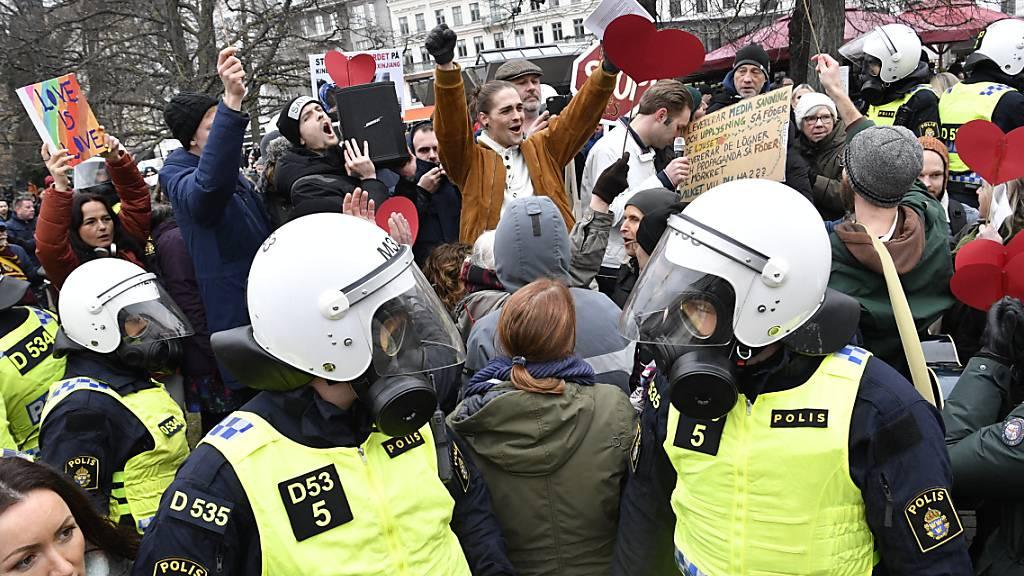 Bereitschaftspolizisten stehen auf einer Straße bei einer Demonstration gegen die Massnahmen zur Eindämmung des Coronavirus. Foto: Johan Nilsson/TT NEWS AGENCY/AP/dpa