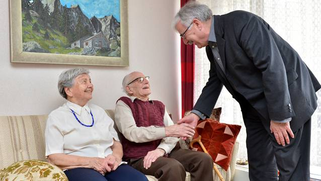 Stadtammann Marcel Guignard gratulliert Werner Wyssmann. Auf dem Bild über dem Ehepaar ist die Nordkante des Badile zu sehen – ein schwieriger Kletterberg.