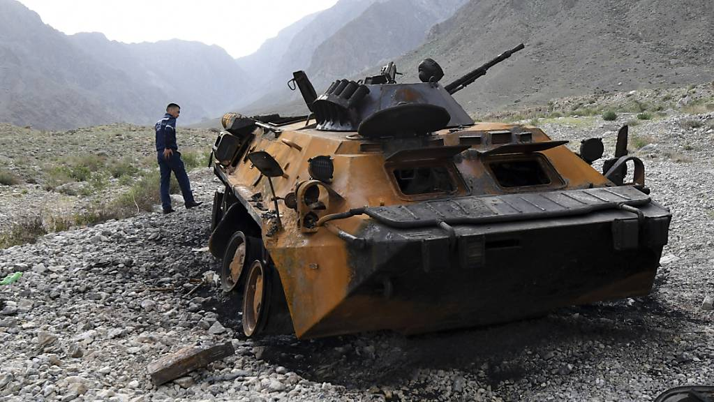 Ein kirgisischer Polizist betrachtet einen verbrannten Panzer nahe der Grenze zwischen Kirgistan und Tadschikistan im Südwesten Kirgistans. Eine Wasserversorgungsanlage ist zum Mittelpunkt des blutigen Grenzkonflikts um den Zugang zu Wasserressourcen in Zentralasien geworden. Foto: Vladimir Voronin/AP/dpa
