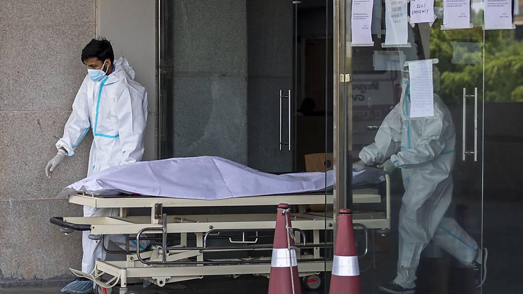 Medizinische Mitarbeiter in Schutzausrüstung transportieren den Leichnam eines Corona-Toten auf einer Trage aus einem Krankenhaus für Corona-Patienten. Foto: Altaf Qadri/AP/dpa