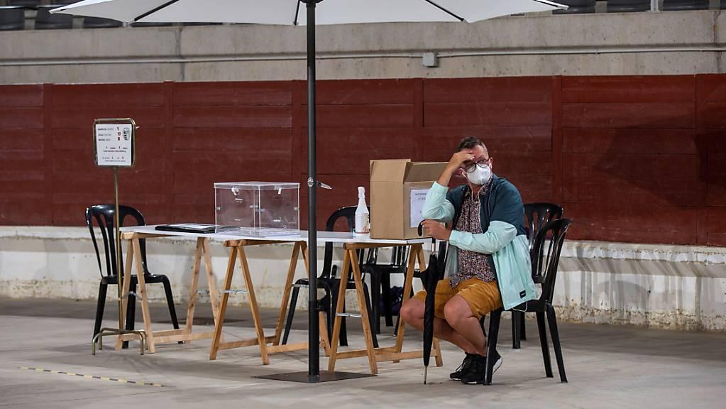 Mit Sonnenschirm und Mundschutz. Ein Wahlhelfer in Vitoria, Baskenland, wartet auf die Wählerinnen und Wähler.
